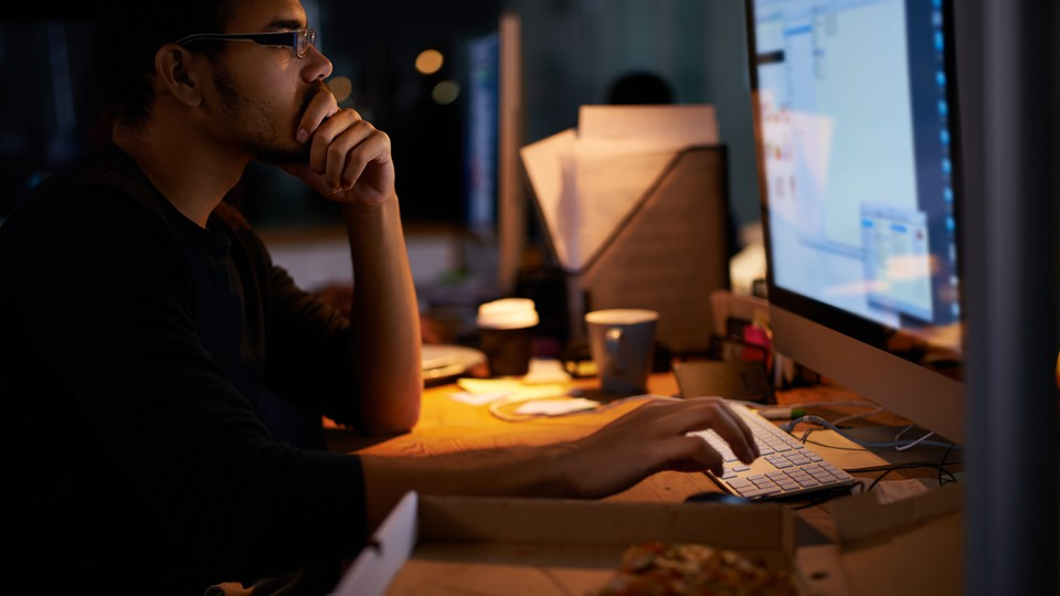 A young man works on a computer in a darkened office.