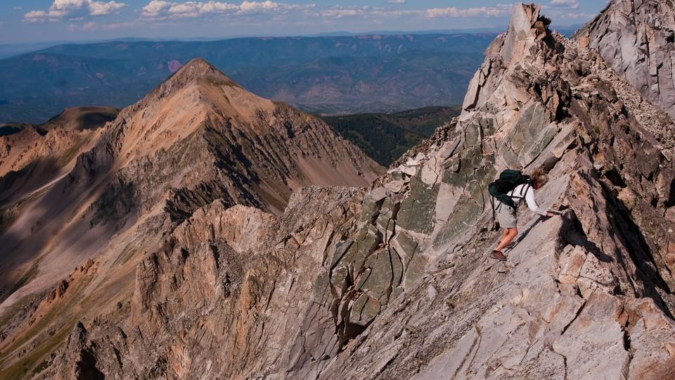 A woman climbing Capitol Peak's Knife Edge