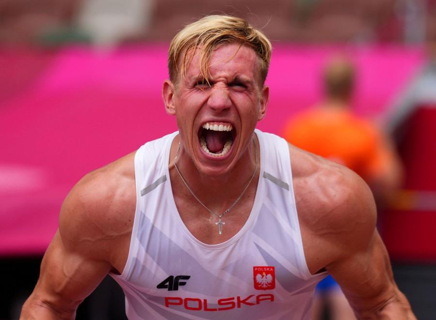 A pole vaulter reacts emotionally after a jump.
