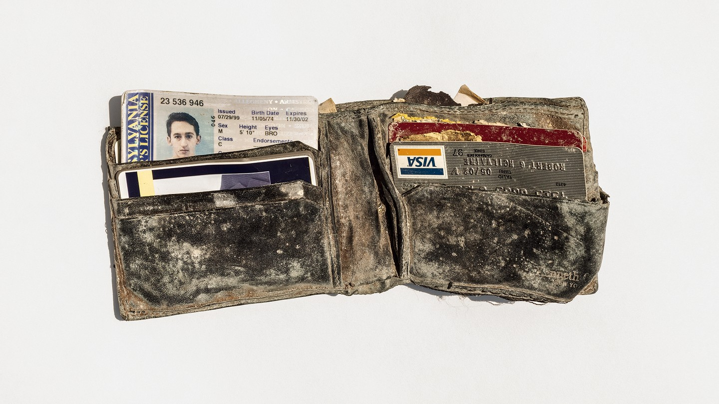 Dusty wallet containing ID, credit card, and other items