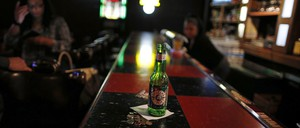 A beer bottle sits on top of a checkered counter at a Chicago bar