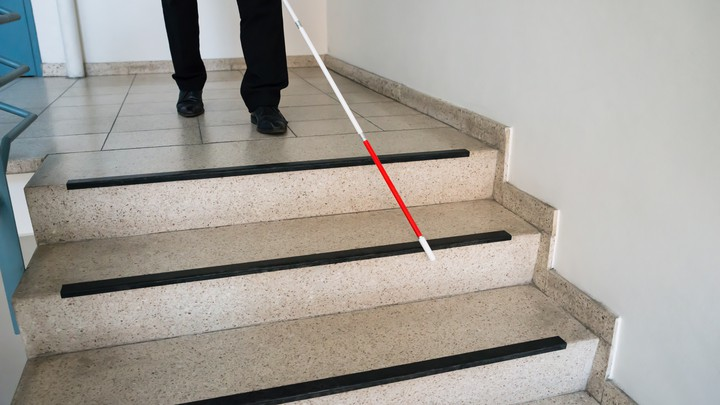 A man walks down a flight of stairs with the help of a white cane.