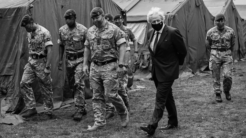 Boris Johnson walks alongside British troops.