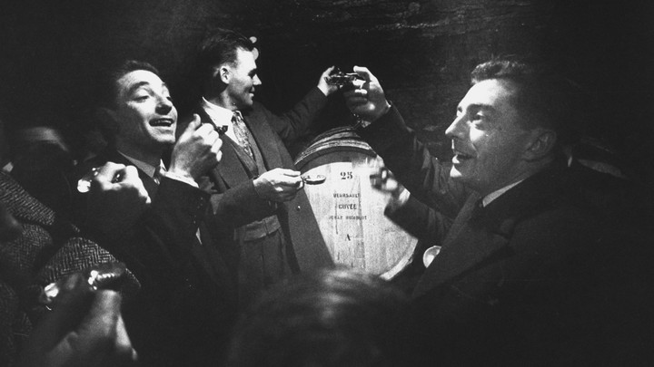 A black-and-white photograph of men in tuxedoes in a wine cave