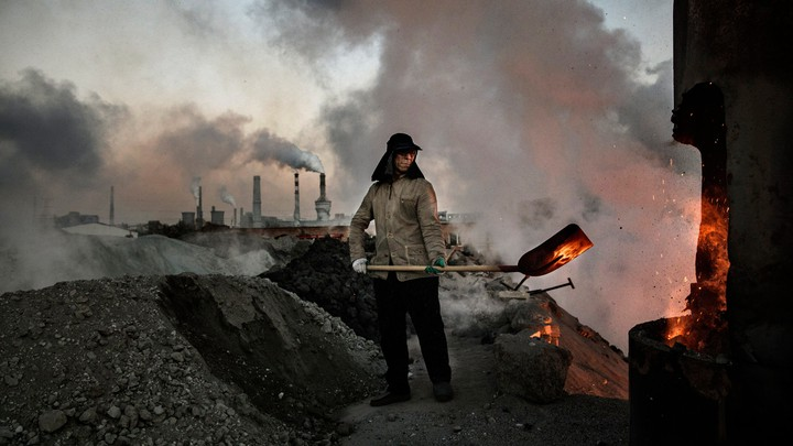 A Chinese labourer loads coal into a furnace as smoke and steam rise from an unauthorized steel factory on November 3, 2016, in Inner Mongolia, China.
