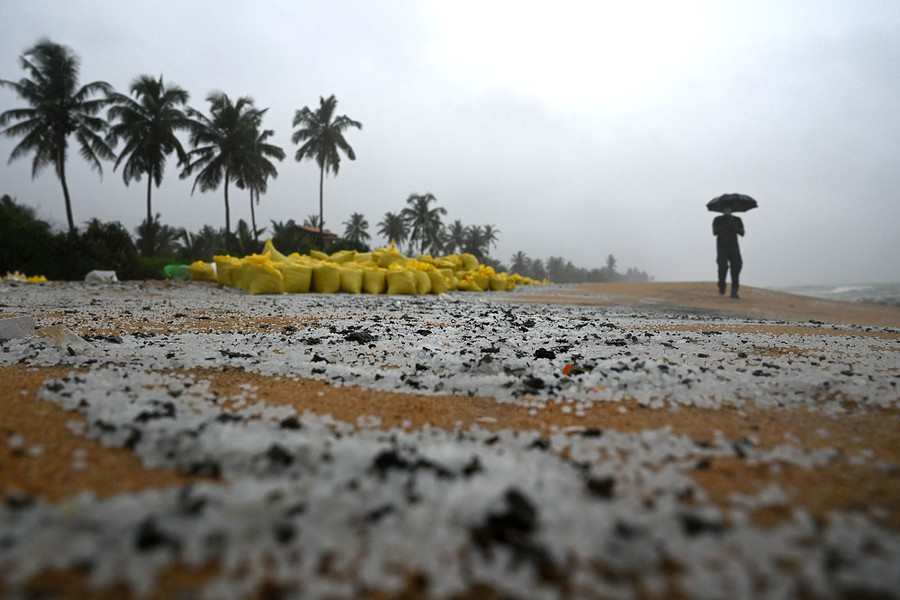 A man walks on a polluted beach past sacks containing debris.