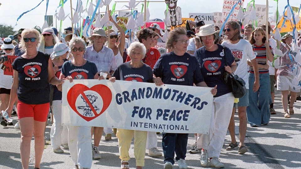 """Protesters hold a sign that says """"Grandmothers for Peace International"""""""