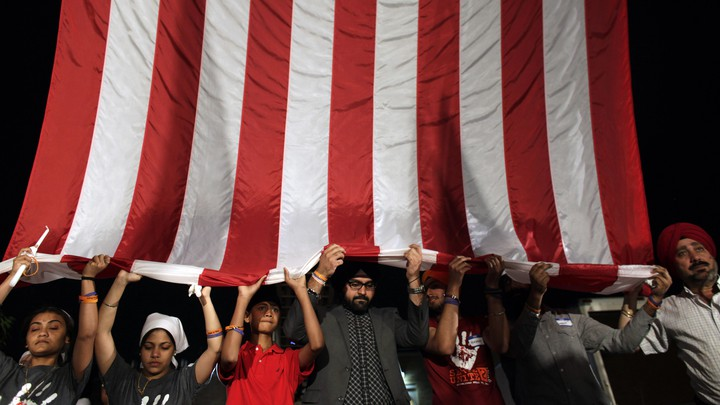 Sikh mourners holding up a large American flag