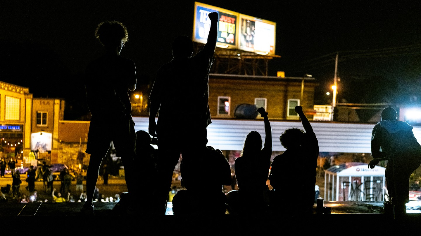 Protesters raise a fist in front of a burning building in Minneapolis.