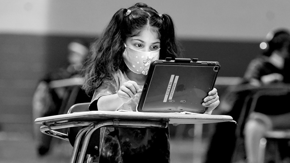 A young girl wearing a mask sits at a desk with an iPad.
