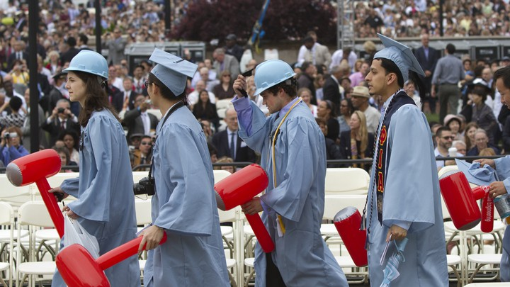Four students walk in light blue commencement caps and gowns.
