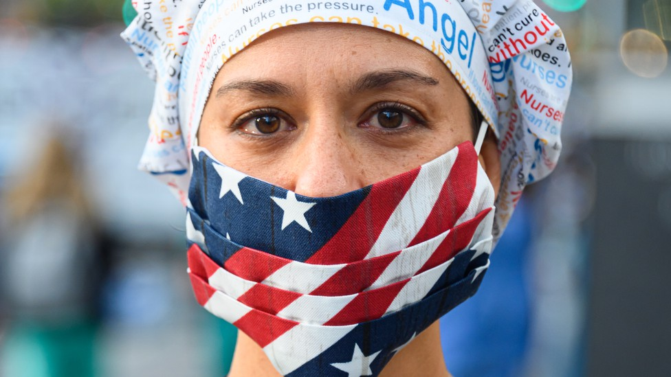 A health worker wearing an American-flag face mask