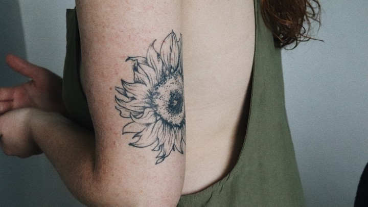A tattoo of a flower on a young woman's upper arm