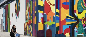 A photo of a young woman riding a bicycle past a colorful mural on the outside of a large building.