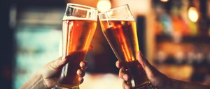 People clink together glasses of beer at a bar.