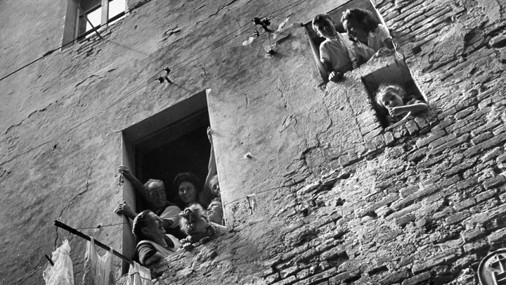 A family looks outside the window of their apartment in Siena, Italy.