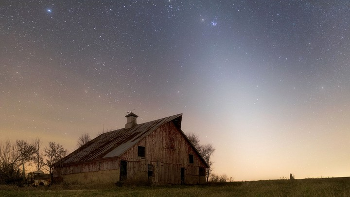 A photograph of an abandoned farm in rural Illinois at night, with the glow of zodiacal light overhead