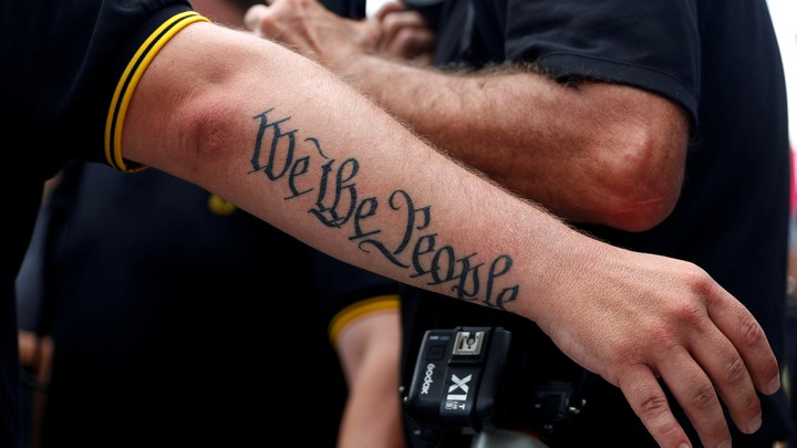 "A person's arm has a tattoo that says ""We The People"""