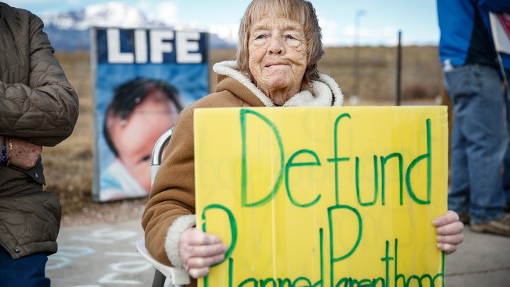 "An older woman holds a yellow sign that says ""Defund Planned Parenthood"" in green letters, with a mountain in the background and people standing beside her"