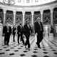 House Speaker Nancy Pelosi, surrounded by aides and security, walks through the Capitol rotunda.