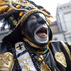 A member of the Krewe of Zulu marches during their parade Mardi Gras day in New Orleans.