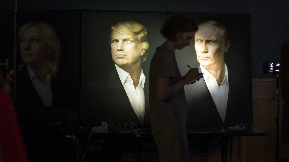 A journalist writes as she watches a telecast of the U.S. presidential election standing at portraits of U.S. presidential candidate Donald Trump and Russian President Vladimir Putin in the Union Jack pub in Moscow, Russia on Nov. 9, 2016.