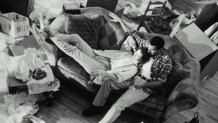 A woman and man cuddle on a couch in a messy room