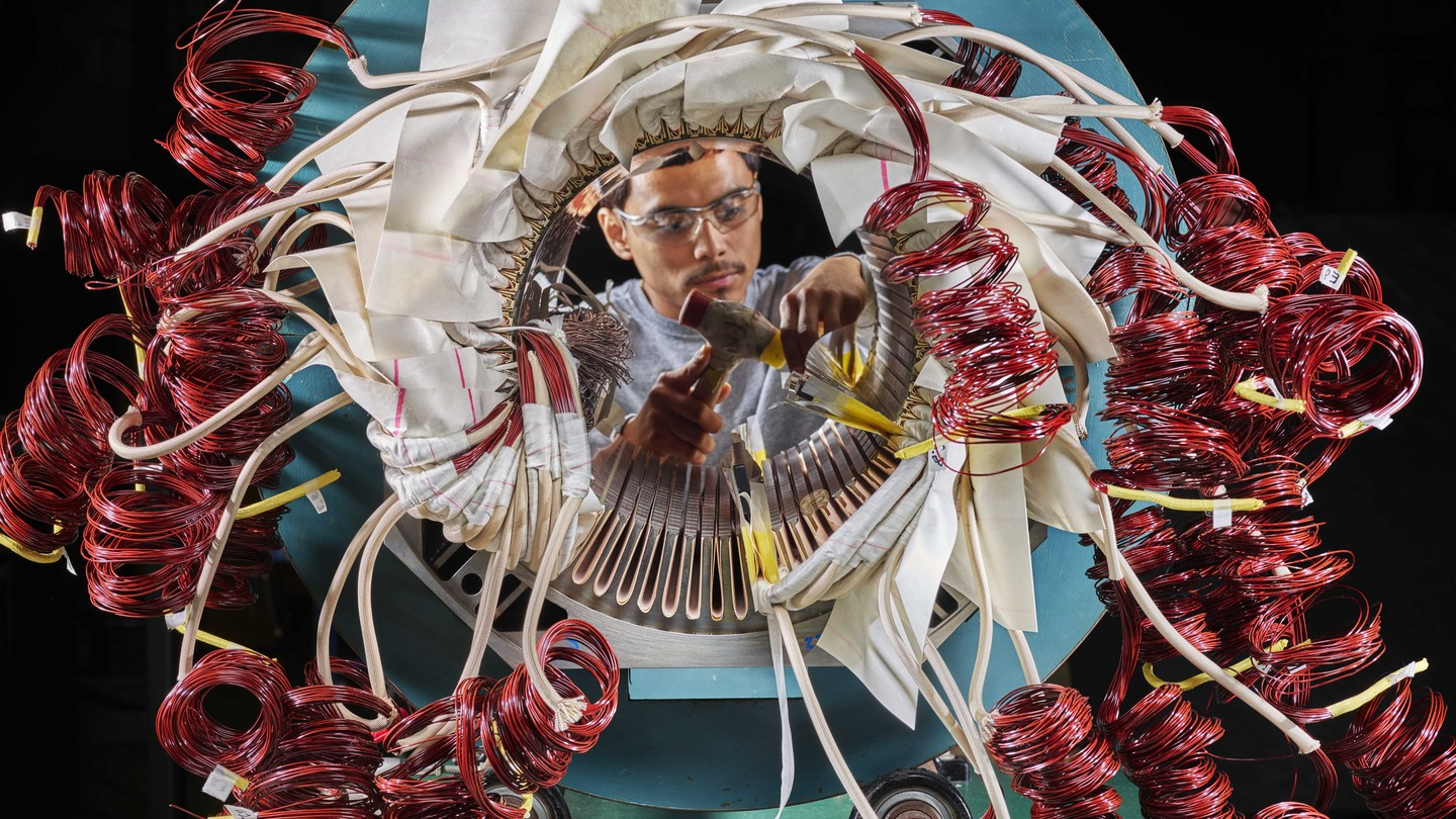 Photo of a person working on a complex motor
