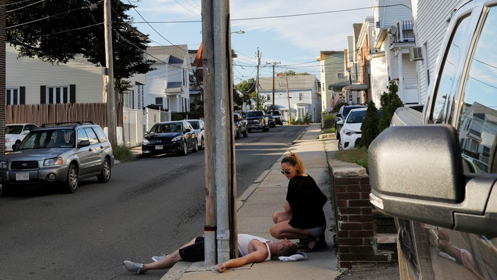 A woman crouches on the sidewalk next to her boyfriend, who is unresponsive and not breathing after an opioid overdose in the Boston suburb of Everett, Massachusetts, on August 23, 2017.