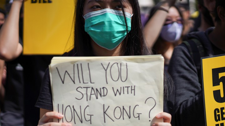 """A woman wearing a face mask holds a placard reading, """"Will you stand with Hong Kong?"""""""
