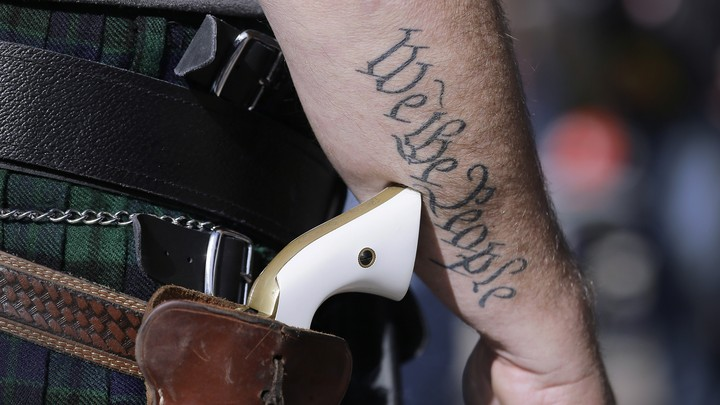 A man wears a pistol as he prepares for a rally in support of open-carry gun laws.