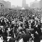 A large crowd packs Independence Mall, with Philadelphia buildings in the background.