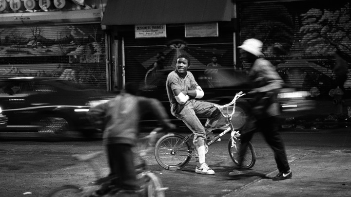 A Black teenager, in focus, sits on a bike with his arms folded, as people and cars around him are blurred.