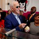 Joe Biden, in sunglasses, smiling with a spoonful of ice cream while surrounded by smiling supporters.
