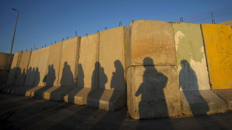 The shadows of Palestinian women at the Qalandiya checkpoint outside the West Bank city of Ramallah
