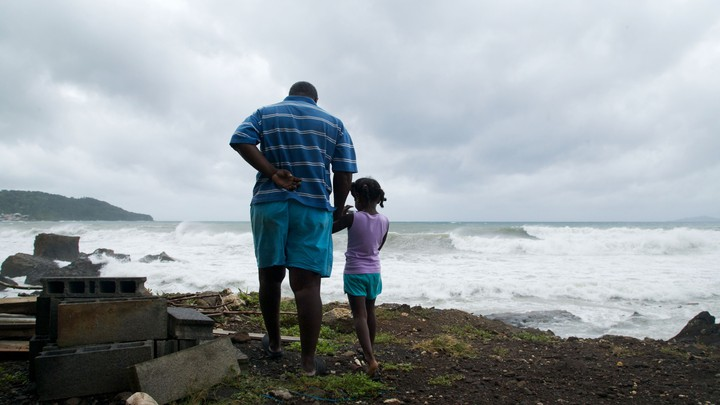 A man and a girl looking at the horizon as a storm approached