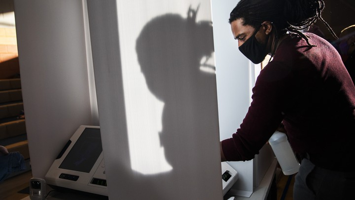 A man cleaning a voting machine for the November 2020 election.