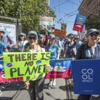 People in matching baseball caps march down a street holding environmental placards.