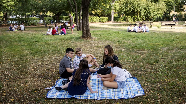 Groups of kids sit spread out on blankets in a park.