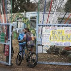 Two people walk through the decorated front gates of a squatter community.