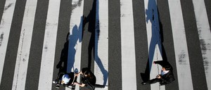 People walk through a crosswalk.