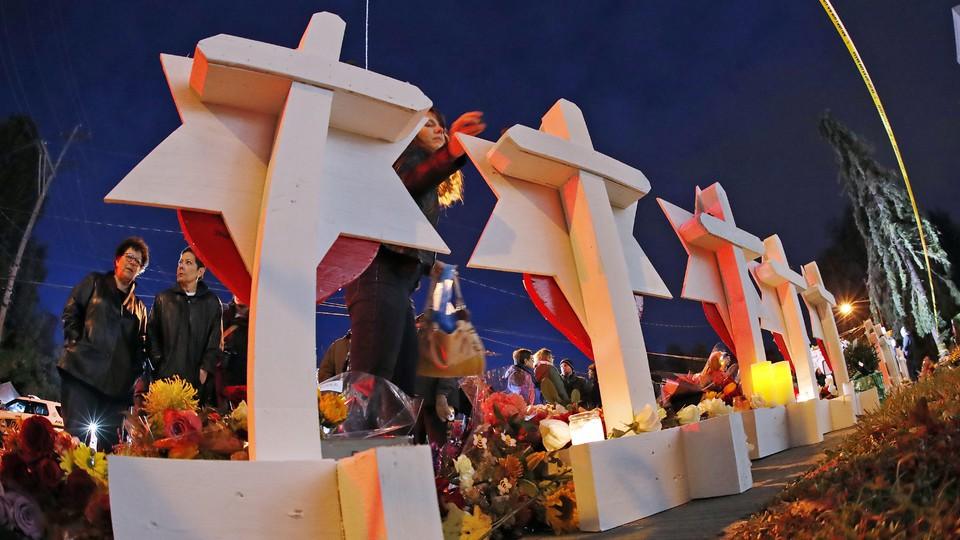 People gather around candlelit memorials.