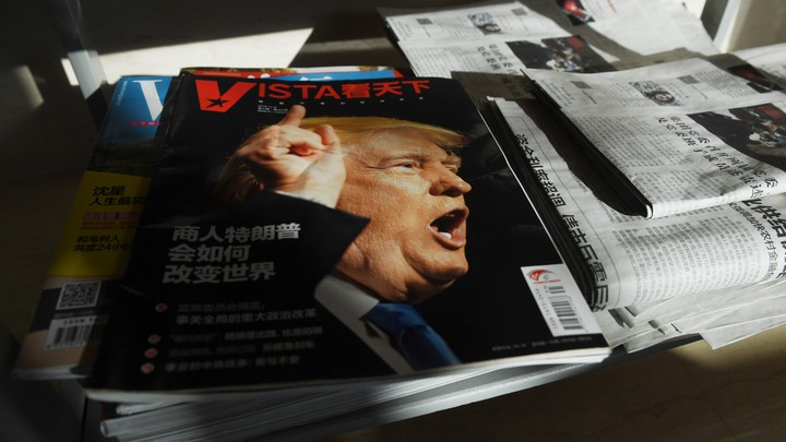 A magazine with a picture of President Donald Trump sits on top of other magazines and newspapers.