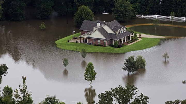 An aerial photo over Amite, Louisiana, shows a home surrounded by water.