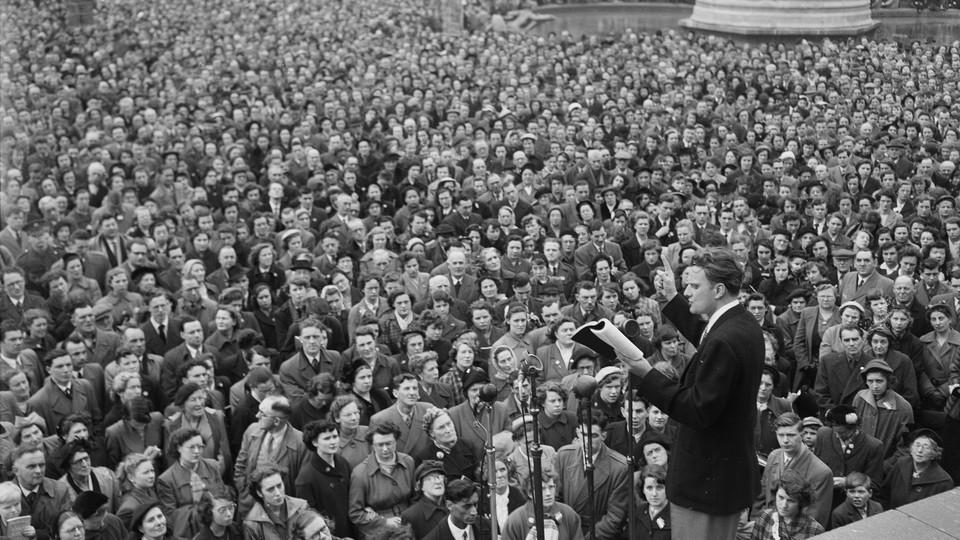 Evangelist Billy Graham, on stage, addresses a crowd.