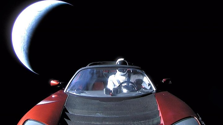 The dummy astronaut Starman, wearing a SpaceX space suit, in the driver's seat of a red Tesla Roadster in space as it speeds away from Earth
