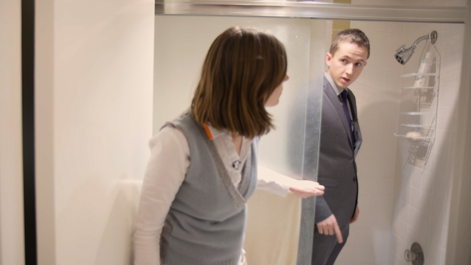 A woman peeking in on James Hamblin, who is fully dressed in a suit, in the shower