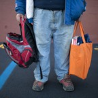 A man holds a backpack and reusable shopping bag full of food from a pantry.
