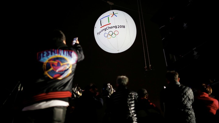 Photographers take photographs of a giant inflatable ball bearing the logo of the 2018 Pyeongchang Winter Olympics.