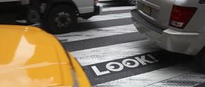 Cars sit in a crosswalk.
